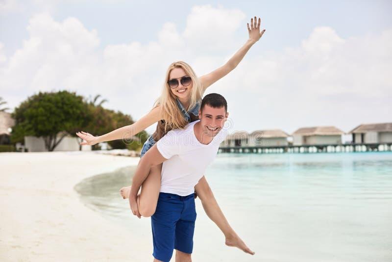 微笑的人运载的妇女画象他的沿海岸 背上给乘驾的人女朋友由海洋 免版税图库摄影