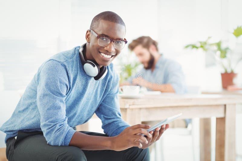 微笑的人画象有耳机的,当使用数字式片剂时 免版税图库摄影