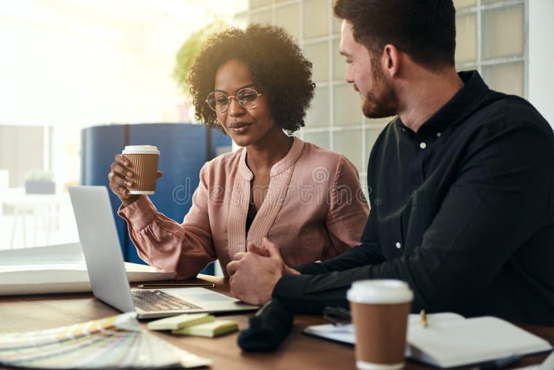 微笑的企业同事与一台膝上型计算机一起使用在办公室 库存图片