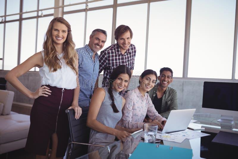 微笑的企业同事画象谈论在膝上型计算机在办公室 库存图片