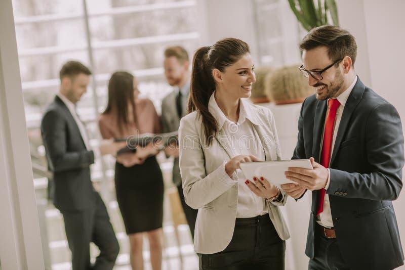 微笑的企业队与数字片剂一起使用在办公室 库存照片