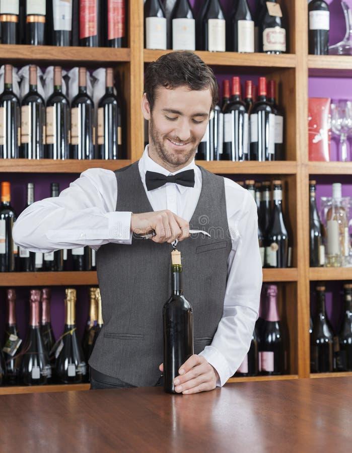 微笑的侍酒者开头酒瓶 免版税库存照片
