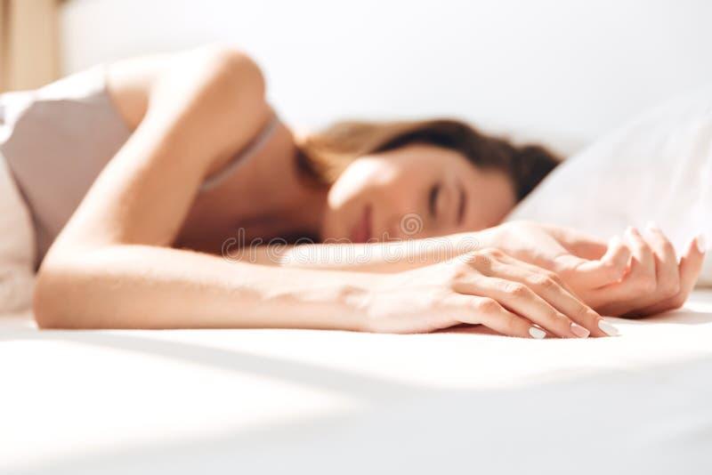 微笑的俏丽的夫人睡眠在床上户内 闭合的眼睛 免版税库存图片