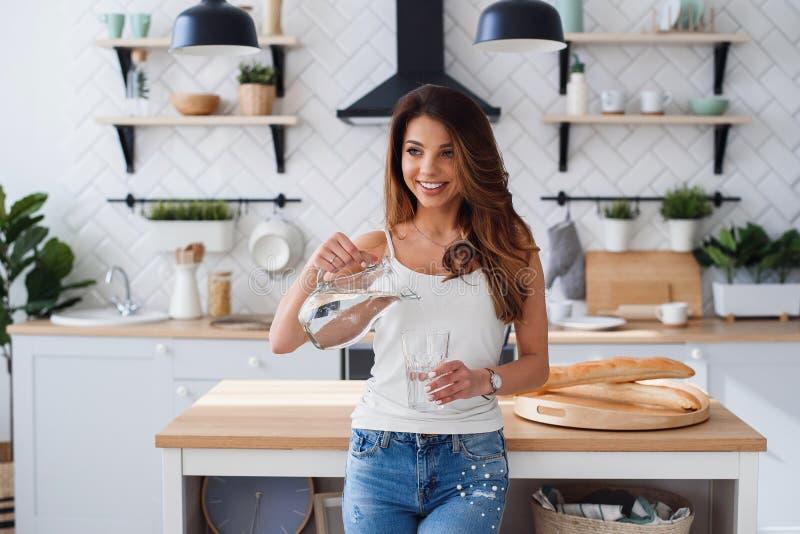 微笑的俏丽的妇女倾吐从瓶的纯净的水入玻璃在厨房里 医疗保健和饮食概念 免版税图库摄影