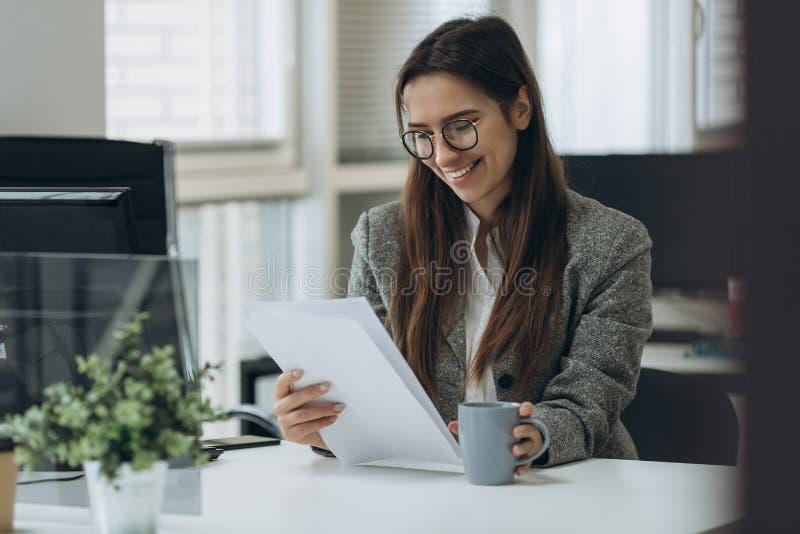 微笑的俏丽的年轻女商人画象玻璃的坐工作场所和与文件一起使用 图库摄影