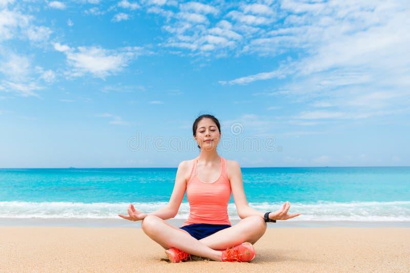 微笑的俏丽的瑜伽妇女坐海边靠岸 免版税库存照片