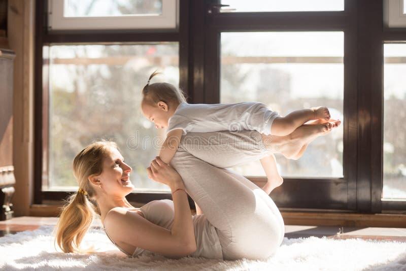 年轻微笑的信奉瑜伽者母亲和她的行使toget的小女儿 库存图片