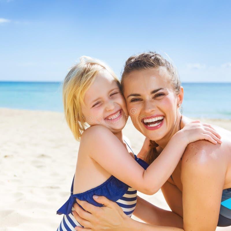 微笑的健康母亲和女儿海滨拥抱的 免版税图库摄影