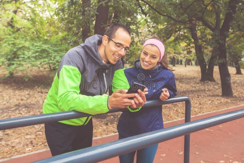 微笑的健身年轻人和妇女在跑以后放松 图库摄影