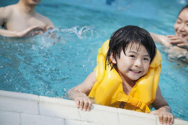微笑的儿子画象在水中和保持水池在背景中渐近与家庭 免版税库存照片