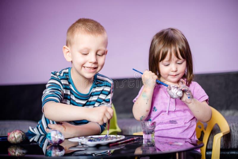 微笑的兄弟和姐妹有水彩的,上色复活节彩蛋 免版税库存照片