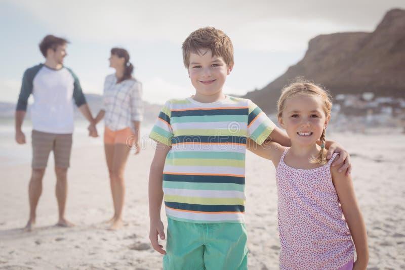 微笑的兄弟姐妹画象有站立在backgeround的父母的 库存图片