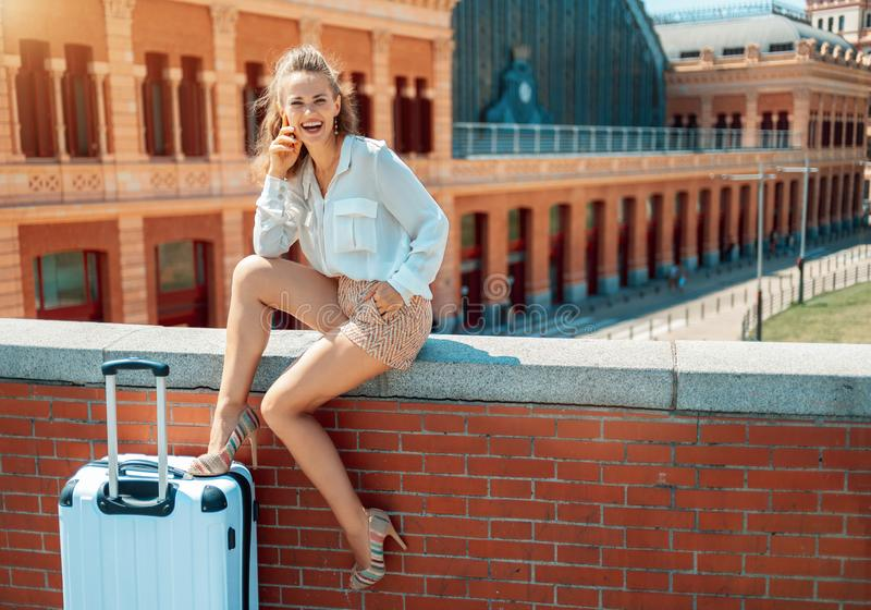 微笑的典雅的旅游妇女,当坐栏杆时 免版税库存图片