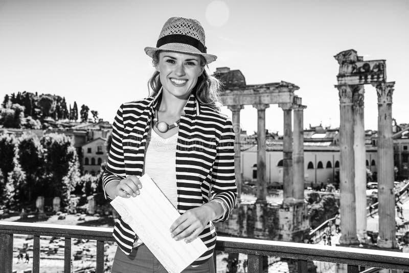 微笑的典雅的旅行家妇女在罗马,有地图的意大利 免版税图库摄影