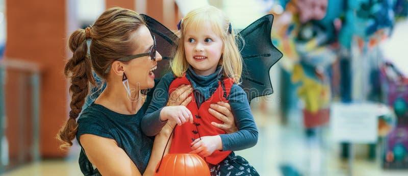 微笑的典雅的母亲和女儿在购物中心的万圣夜 免版税库存照片