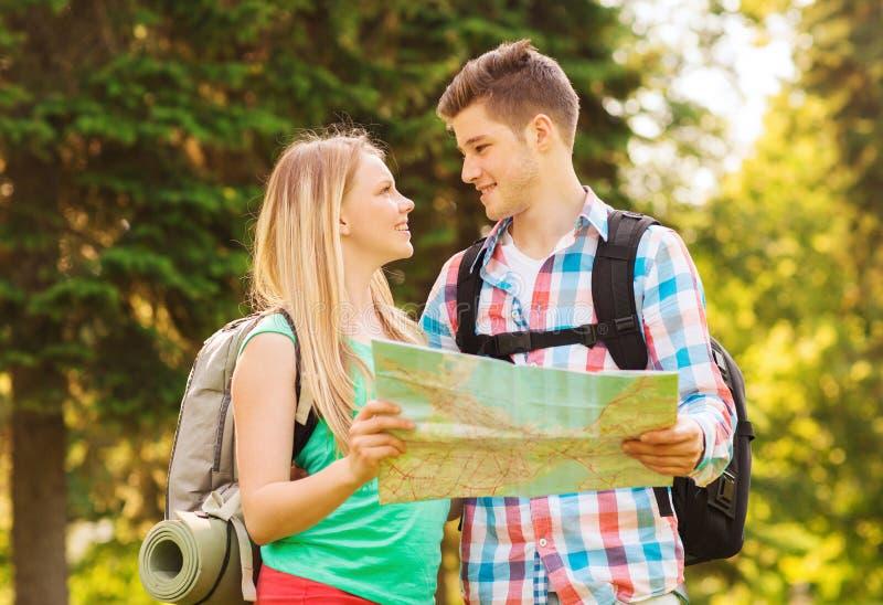 微笑的加上地图和背包在森林里 免版税图库摄影