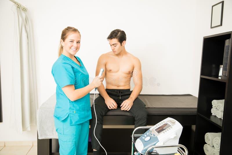 微笑的医生Giving Customer Ultrasound Treatment在医院 免版税库存照片