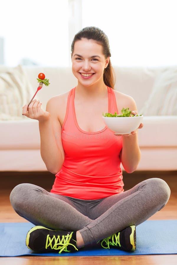 微笑的十几岁的女孩用蔬菜沙拉在家 库存图片