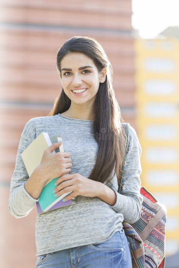微笑的十几岁的女孩画象有书的在校园 免版税库存照片