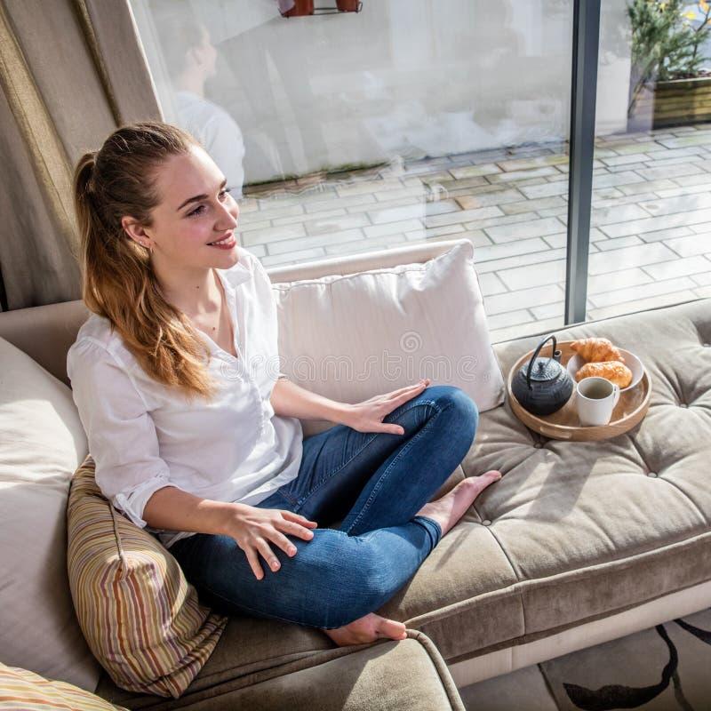 微笑的华美的少妇坐有早餐的舒适的沙发 库存照片