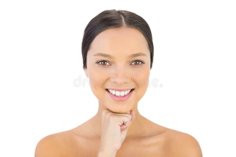 微笑的华美的浅黑肤色的男人用在下巴摆在下的手 免版税库存图片