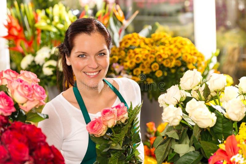 微笑的卖花人花店五颜六色的做的花束 库存图片
