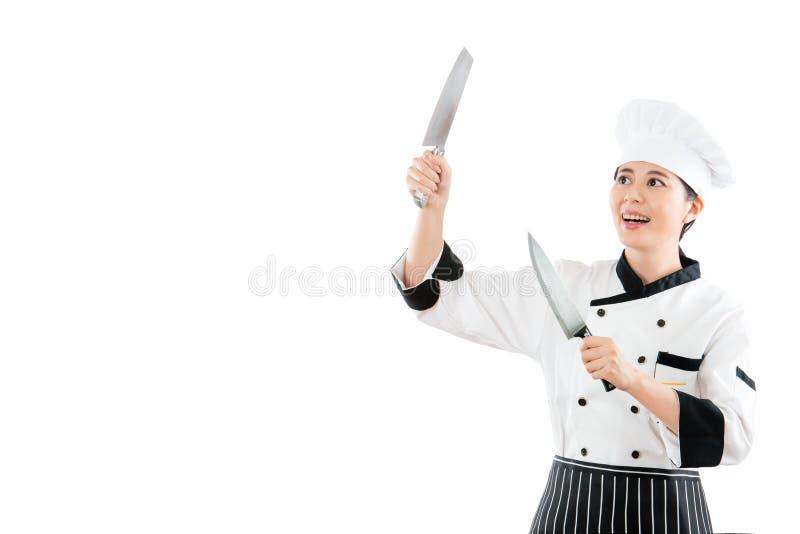微笑的厨师在天空中的拿着两把刀子 库存照片