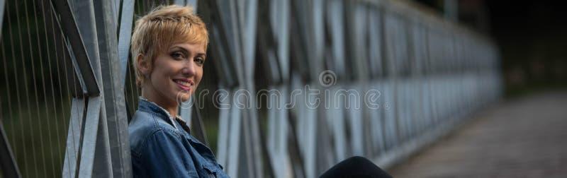 微笑的友好的年轻白肤金发的妇女全景 图库摄影
