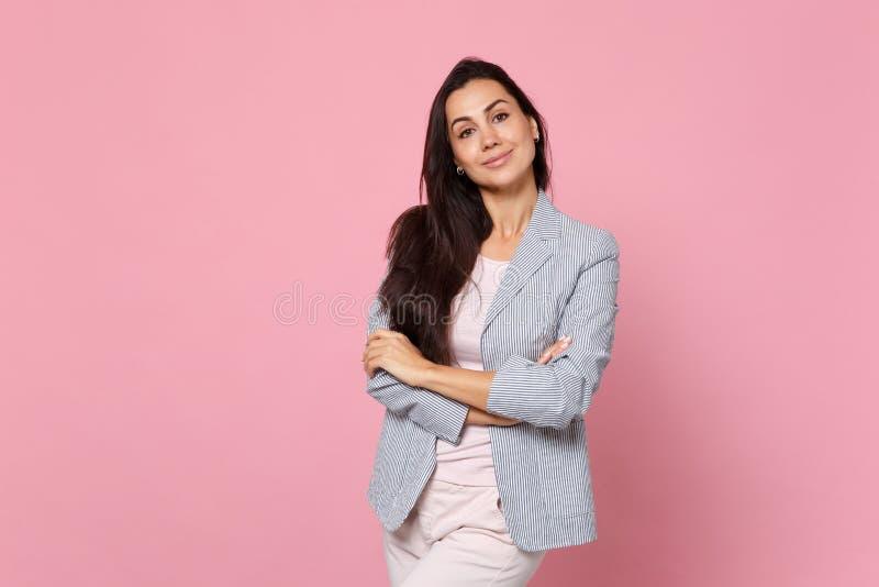 微笑的可爱的年轻女人画象握手的镶边夹克的折叠隔绝在桃红色淡色墙壁上 免版税库存照片