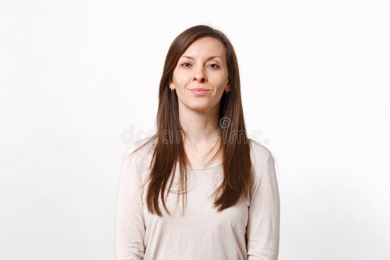 微笑的可爱的年轻女人画象站立和看照相机的轻的衣裳的隔绝在白色墙壁上 免版税库存照片