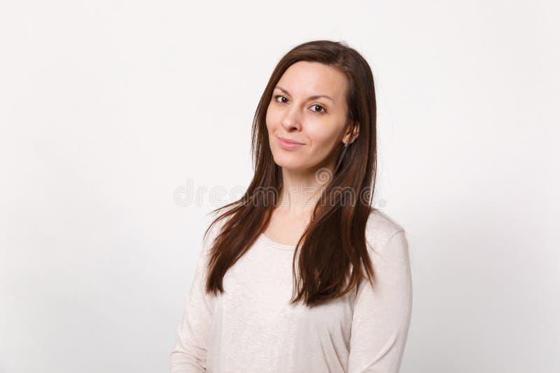 微笑的可爱的年轻女人画象站立和看照相机的轻的衣裳的隔绝在白色墙壁上 库存图片