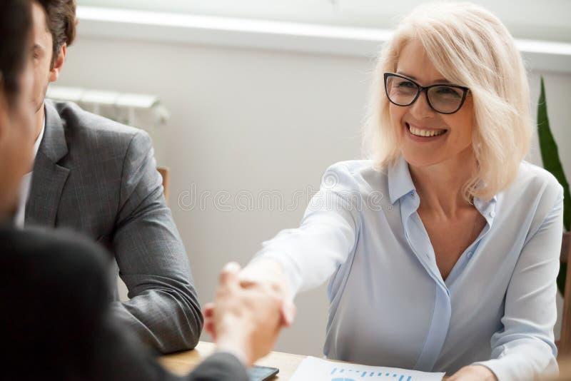 微笑的可爱的成熟女实业家握手商人 免版税库存图片