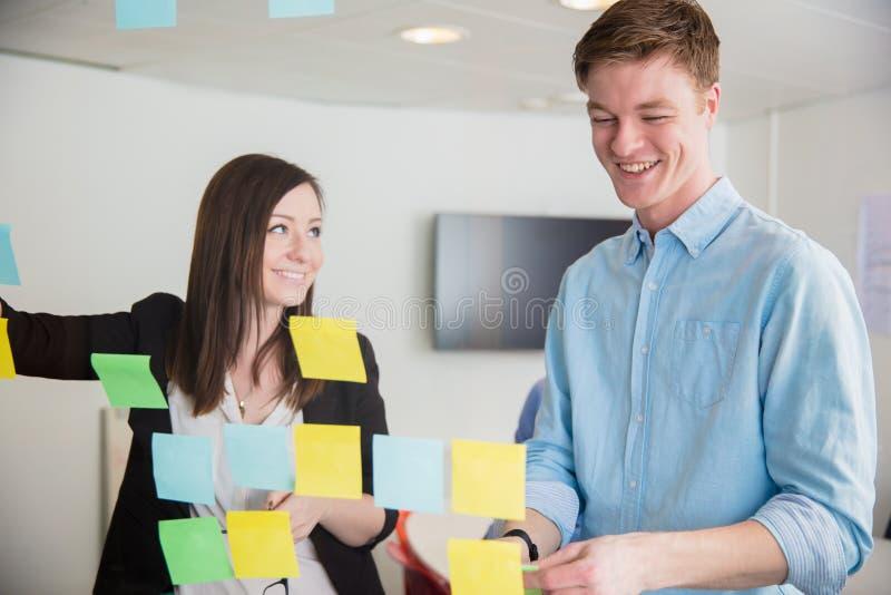 微笑的同事,当谈论在笔记在玻璃时黏附了 免版税库存照片