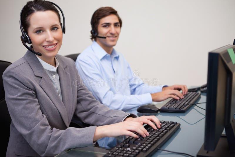微笑的呼叫中心座席侧视图在工作 免版税库存图片