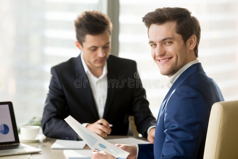 微笑的商人、看a的金融分析员或者股票经纪人 库存图片