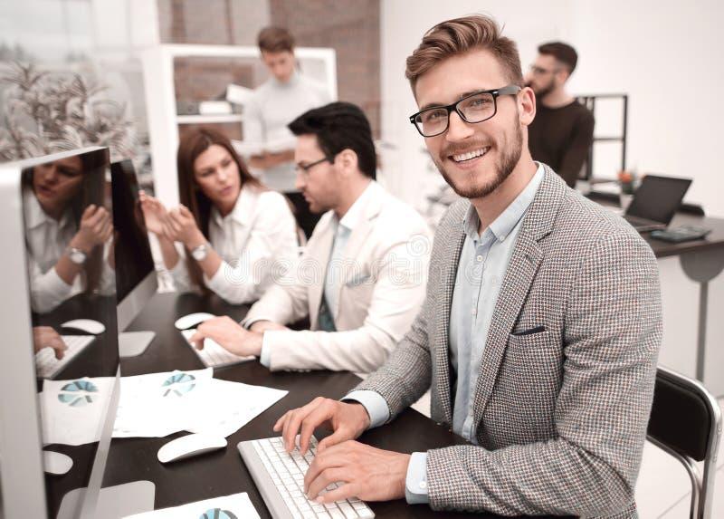 微笑的商人使用一台计算机分析财务数据 库存图片