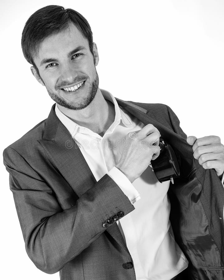 微笑的商人在他的口袋掩藏一个闹钟并且看 库存照片