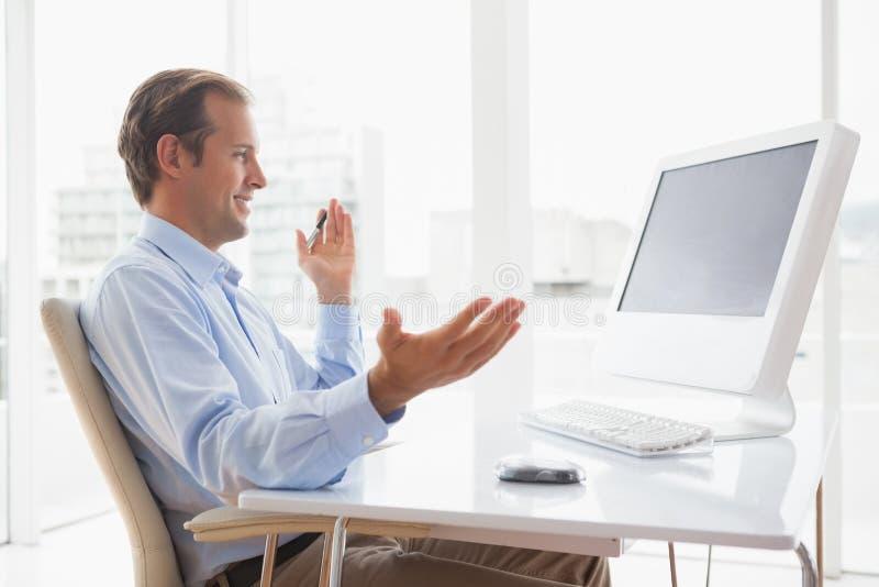 微笑的商人在他的书桌坐录影闲谈 图库摄影