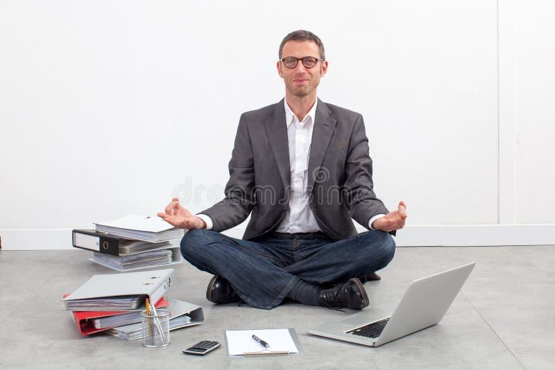 微笑的商人实践的瑜伽在放松的办公室 库存图片