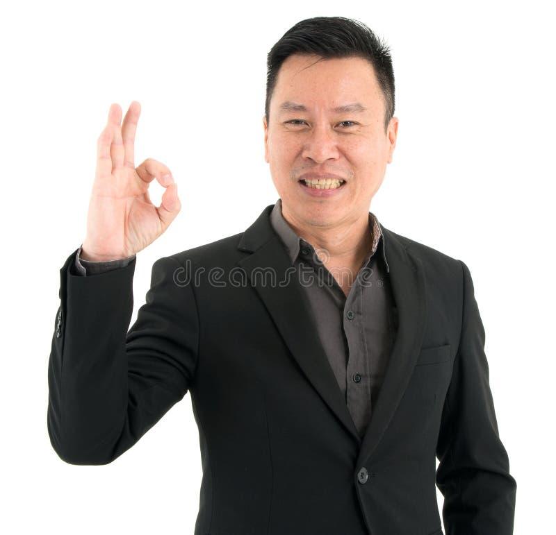 微笑的商人当前信心陈列OK手指画象,隔绝在白色背景 免版税库存图片