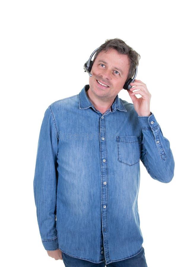微笑的商人谈话与在电话中心操作员的耳机工作 免版税库存照片