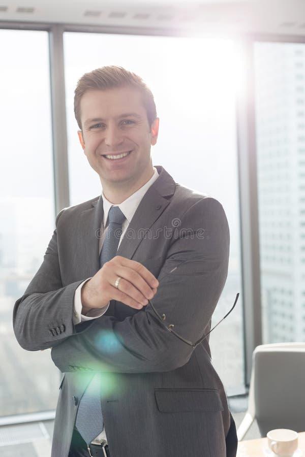 微笑的商人身分画象与镜片的在办公室 库存图片