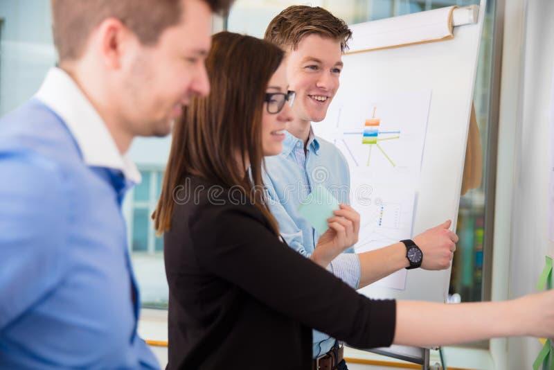 微笑的商人,当女性行政举行的黏着性笔记时 免版税图库摄影