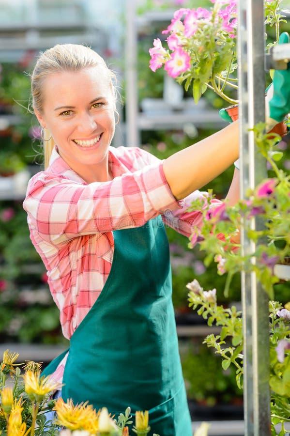 微笑的园艺中心妇女运作的盆的花 免版税库存照片