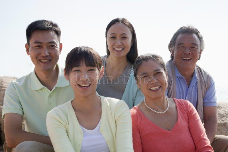 微笑的多代家庭画象坐岩石户外,中国 免版税图库摄影