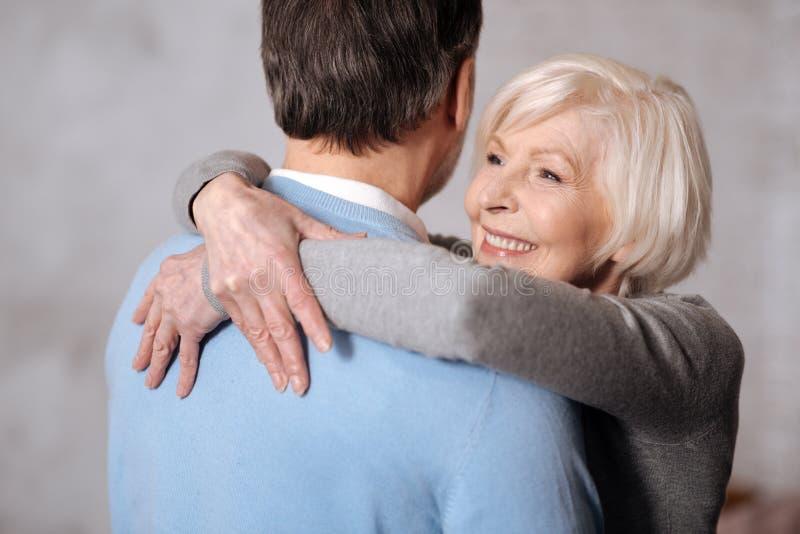 微笑的夫人拥抱的丈夫特写镜头  免版税库存图片