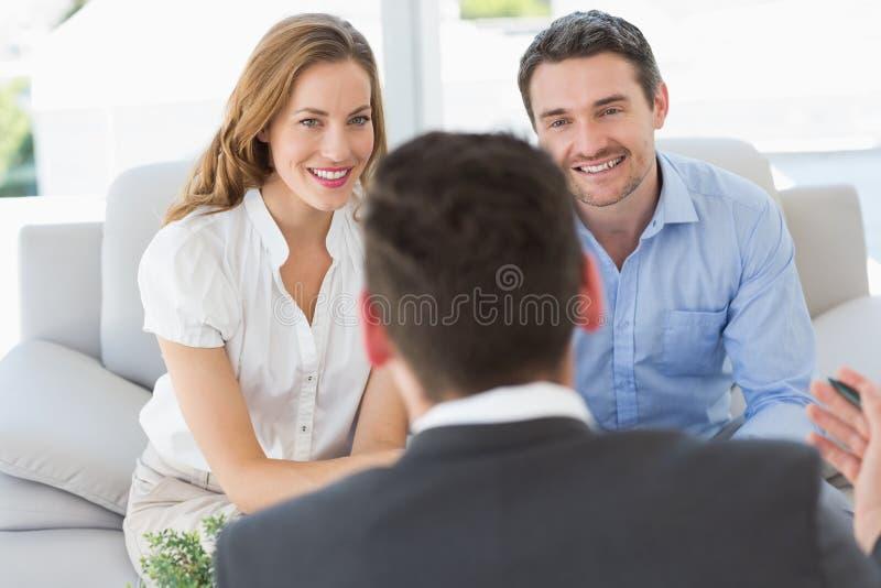 微笑的夫妇在与一位财政顾问的会谈 免版税库存图片