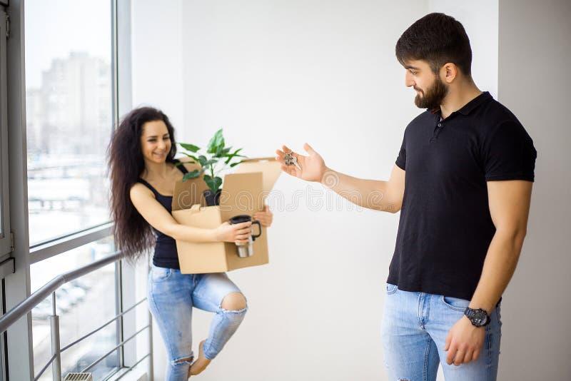 微笑的夫妇在新的家打开箱子 免版税库存照片
