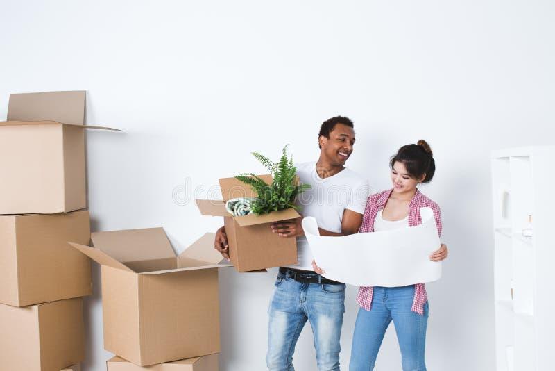 微笑的夫妇在新的家打开箱子 库存图片
