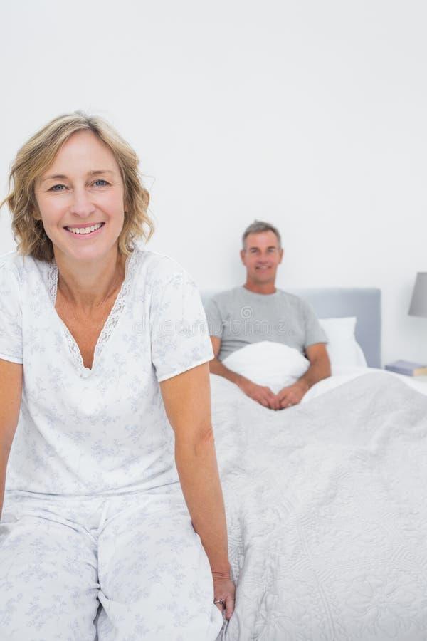 微笑的夫妇坐床的相反方 库存照片